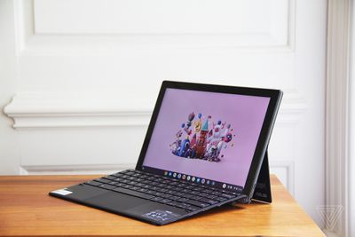 The Asus Chromebook Detachable CM3 open, angled to the left. The screen displays a cartoon city scene on a pink background.