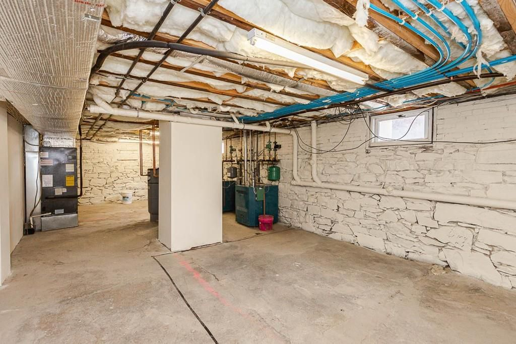 An unfinished and largely empty basement with concrete floors.