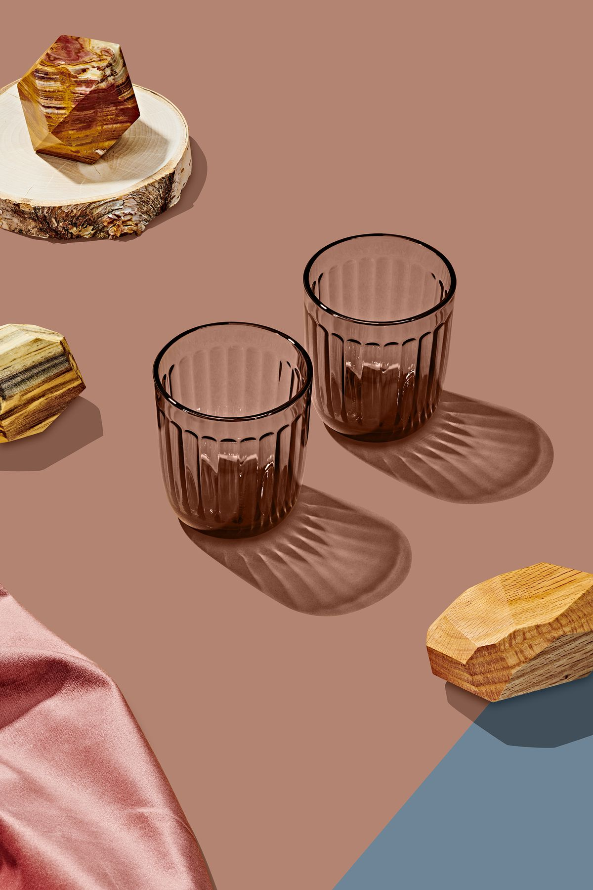 Two glass tumblers which are part of the Curbed Holiday Gift Guide 2019. The tumblers have ridges on the sides but are smooth to the touch. Around the tumblers are various design objects on a taupe surface.