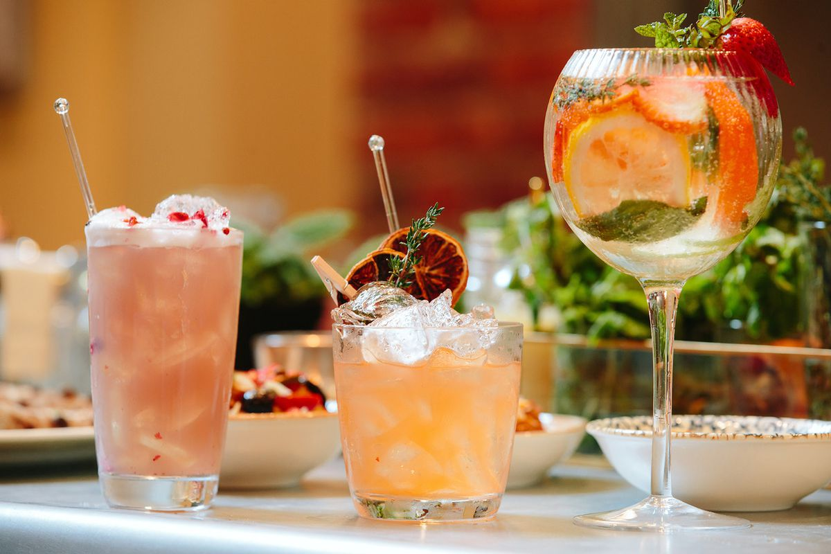 Three colorful cocktails sit on a table with food visible in the background