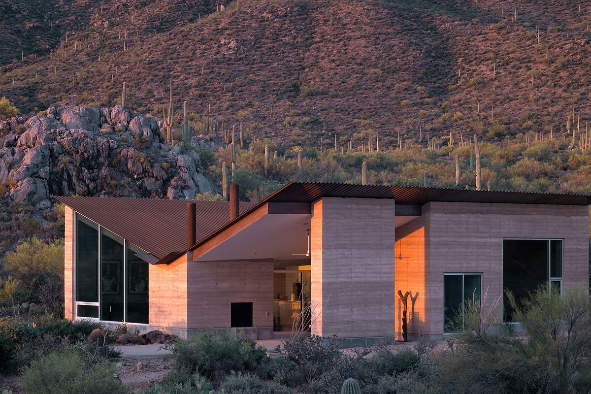 A modern home with a corrugated metal butterfly roof and earthen walls set in the desert.