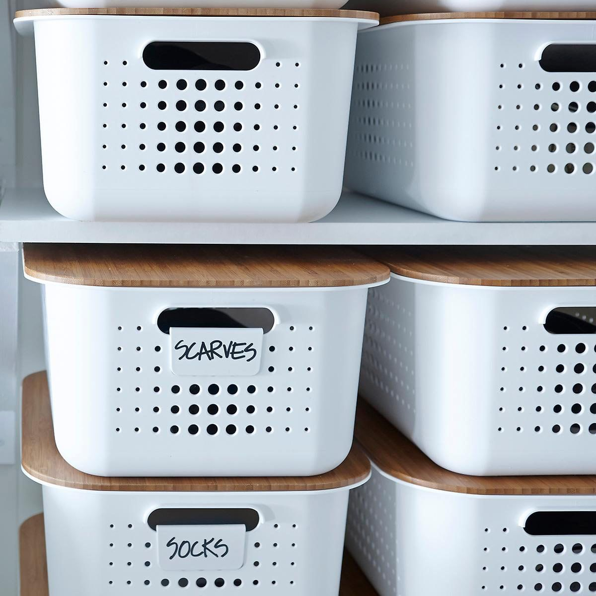 A stack of white bins with holes.
