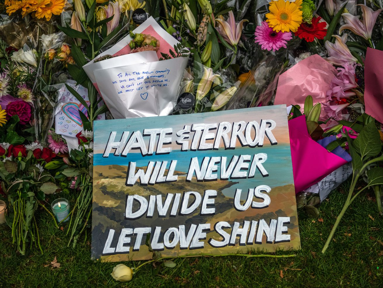 A message is left amongst flowers and tributes by wall of the Botanic Gardens on March 17, 2019 in Christchurch, New Zealand. 50 people are confirmed dead, with 36 injured still in hospital following shooting attacks on two mosques Friday.