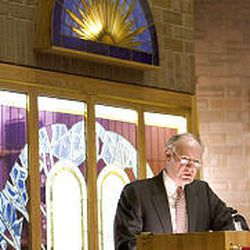 Elder Scott Parker reads from the Book of Mormon during Sunday evening's service.