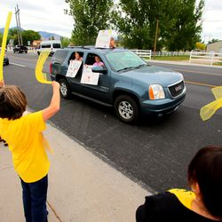 Teachers at Farr West Elementary in Farr West, Weber County, wave scarves at students and their parents during a drive-by parade in front of the school on the last day of classes on Friday, May 15, 2020.