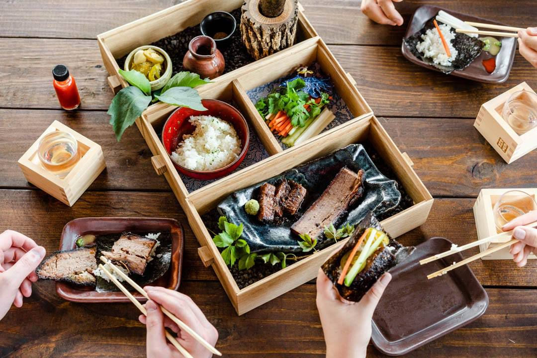 An open wooden box with four compartments filled with various dishes with food, surrounded by dishes outside of the box with food and hands picking up food with chopsticks
