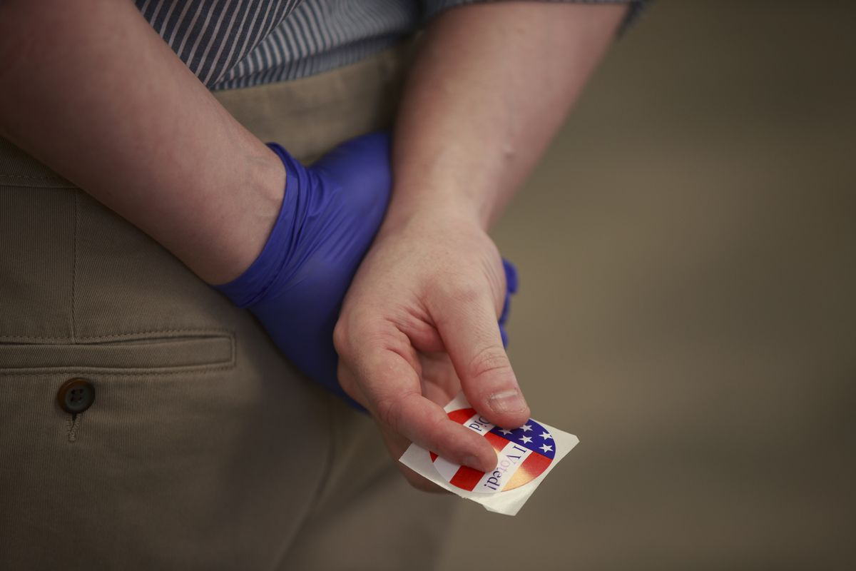"""A voter wearing a glove holds an, """"I Voted,"""" sticker during..."""