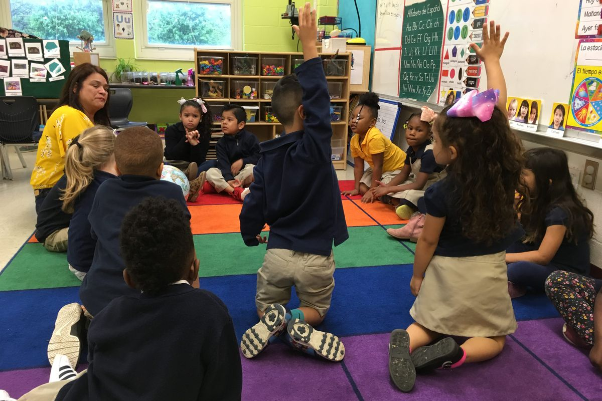 Pre-K students raise their hands during morning circle time at a new bilingual prekindergarten class at Global Preparatory Academy in Indianapolis.