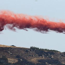 A small plane drops retardant on a fire burning at the mouth of Weber Canyon on Tuesday, Sept. 5, 2017.