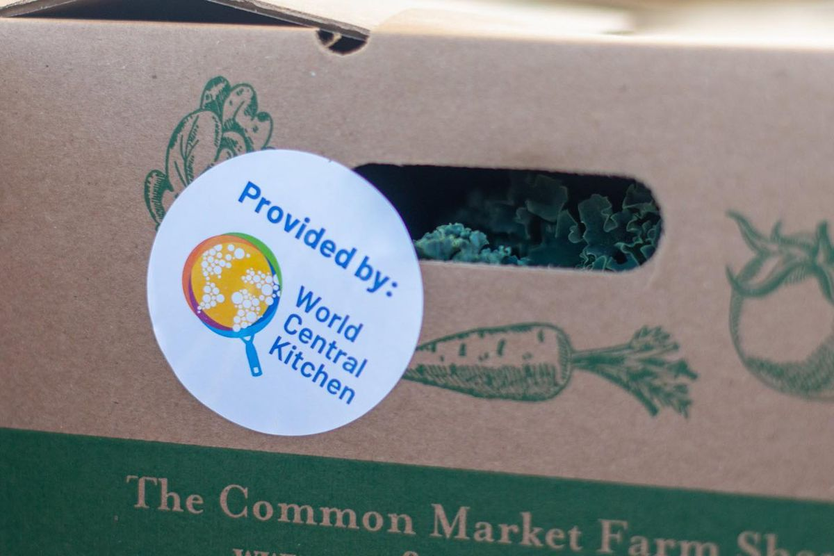 """A box of fresh produce prepared for distribution. A circular white sticker reads """"Provided by: World Central Kitchen"""""""