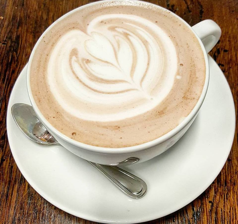 A hot chocolate in a large white mug on a saucer with heart-shaped foam art