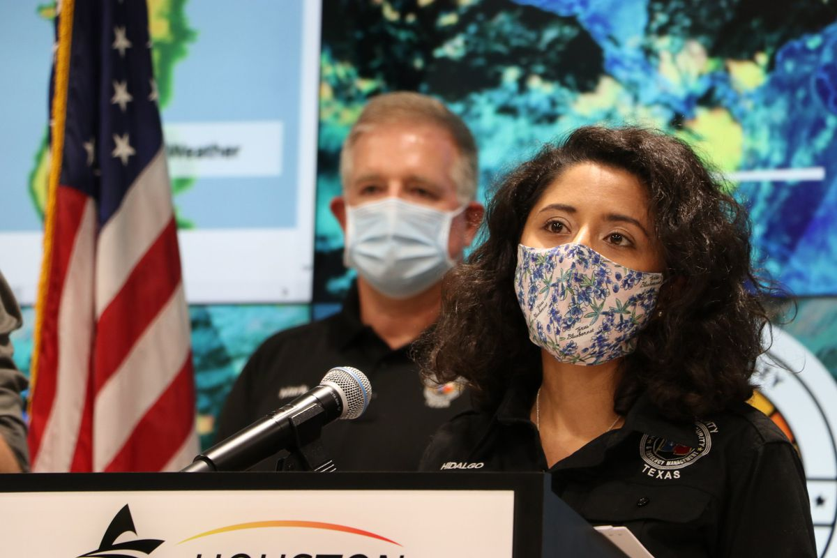 A Latinx woman stands at a podium wearing a mask printed with blue flowers