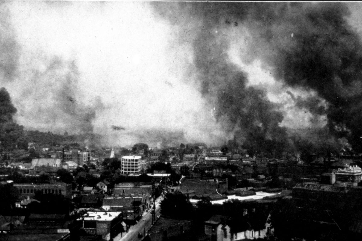 Smoke billows as the city burns, seen from a distant rooftop.