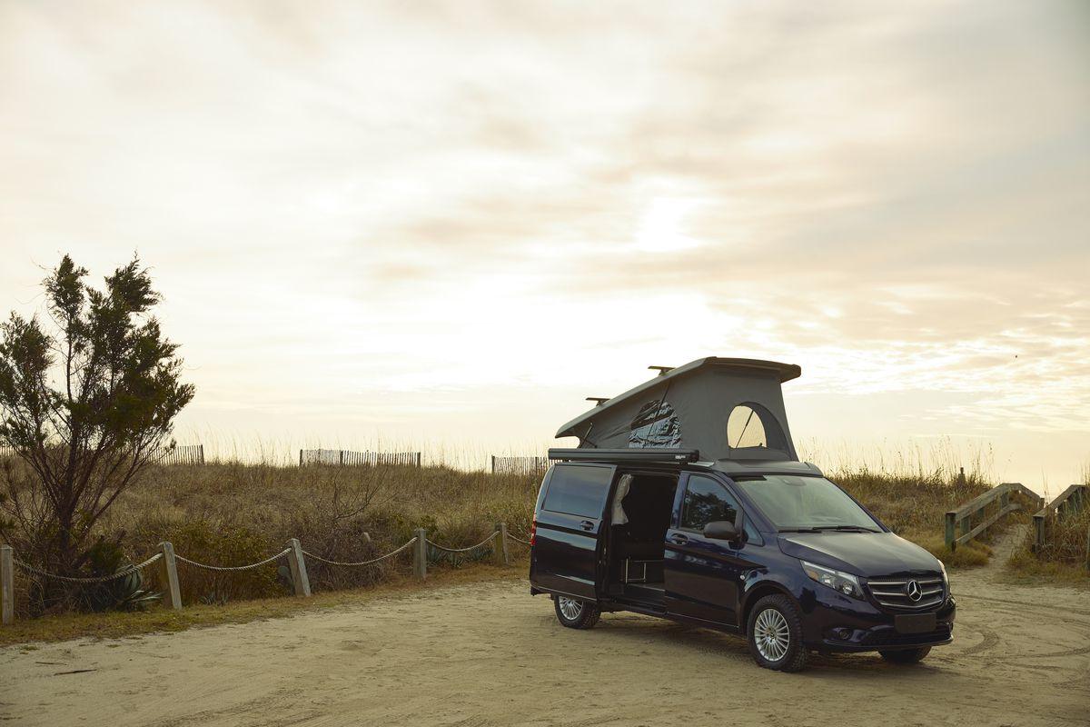An external view of Mercedes-Benz minivan with a pop-top camper roof sitting in a dirt parking lot.