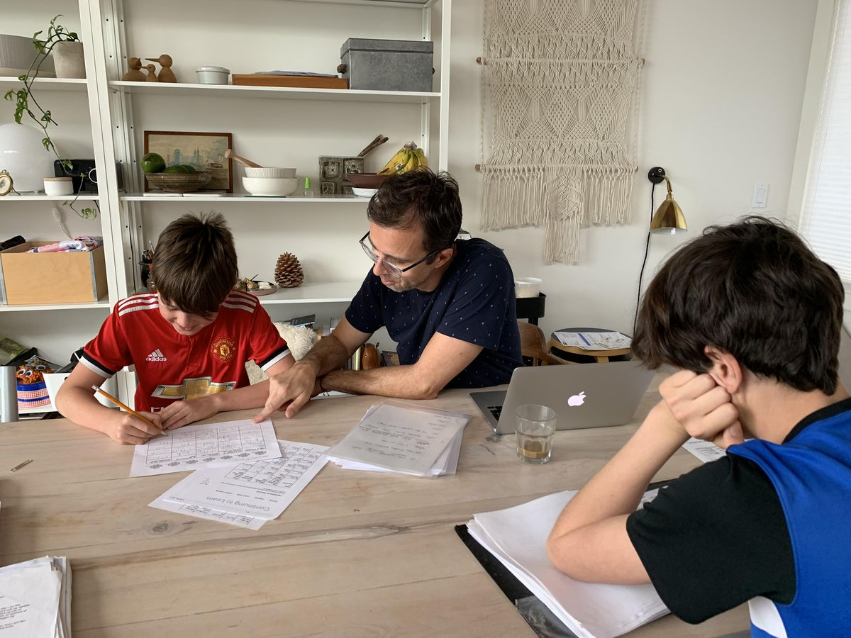 The Kantine chef's boys sit at the table during a homeschooling session with their dad, Joachim Majholm
