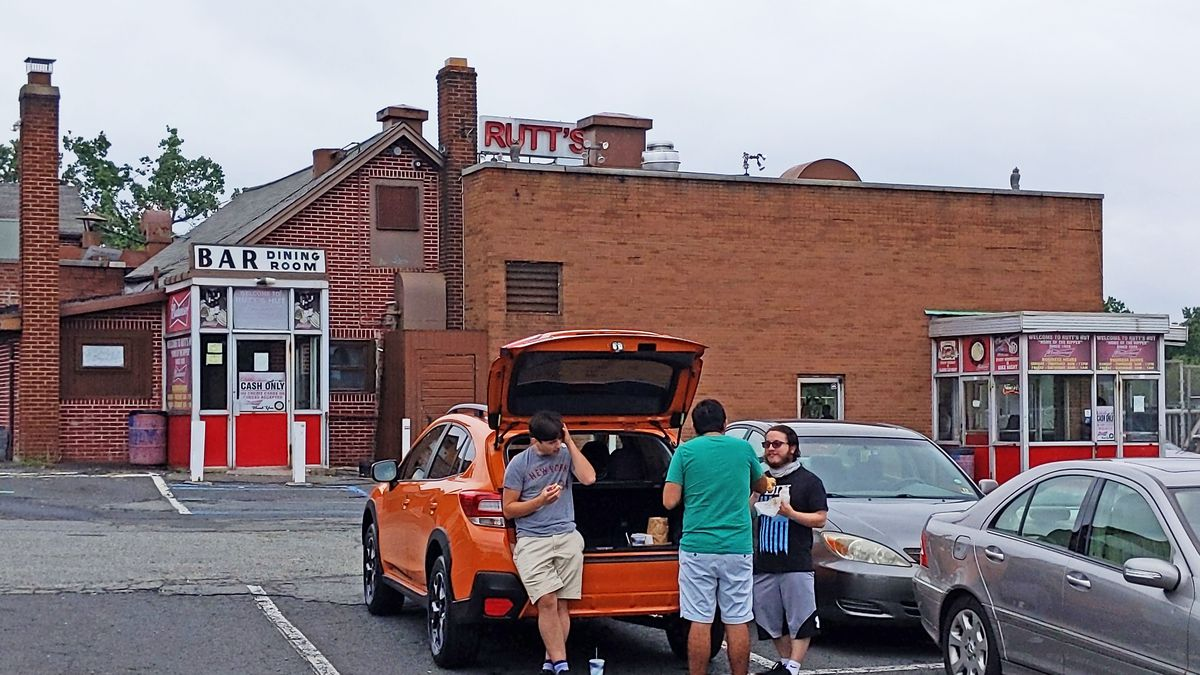 Three people stand eating on the tailgate of an orange car in front of the restaurant.