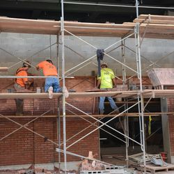 5:12 p.m. Red bricks continue to be fitted, along the Sheffield Avenue wall -