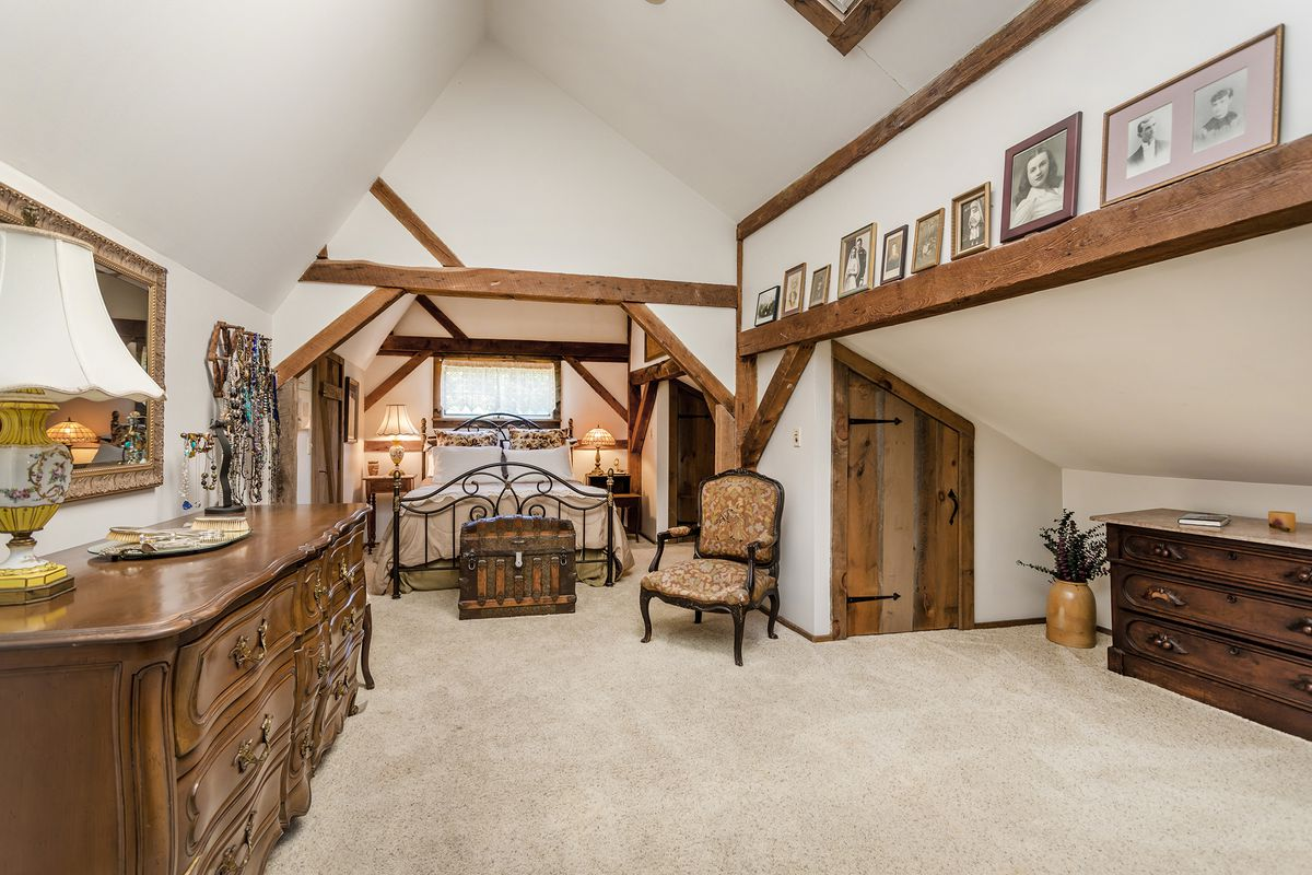 The master bedroom has white walls, exposed wood beams, and antique furniture.