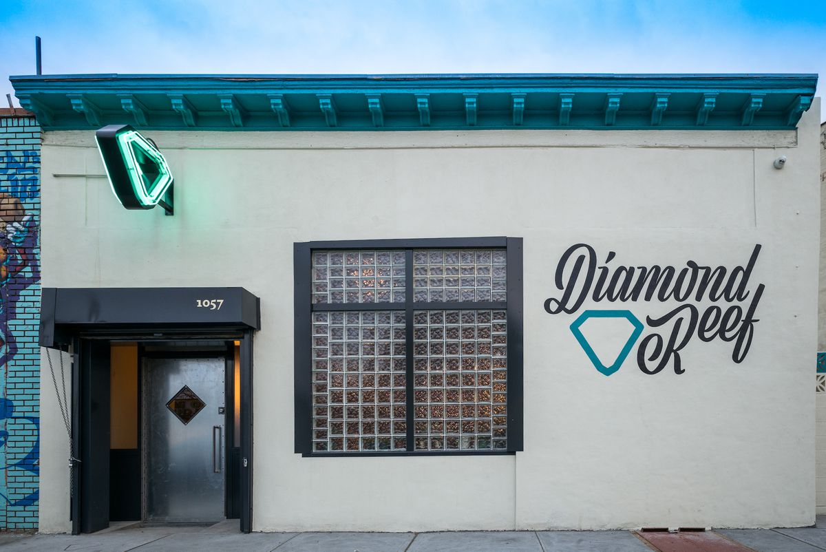 The white exterior of Diamond Reef bar, with a door in the bottom left corner of the building