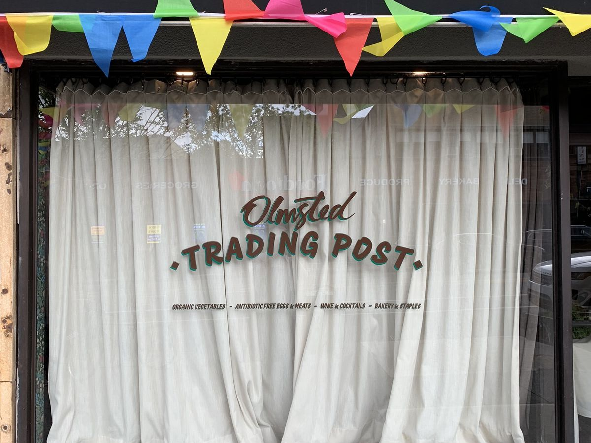 The exterior of a restaurant and its glass window with the text Olmsted Trading Post printed in gold