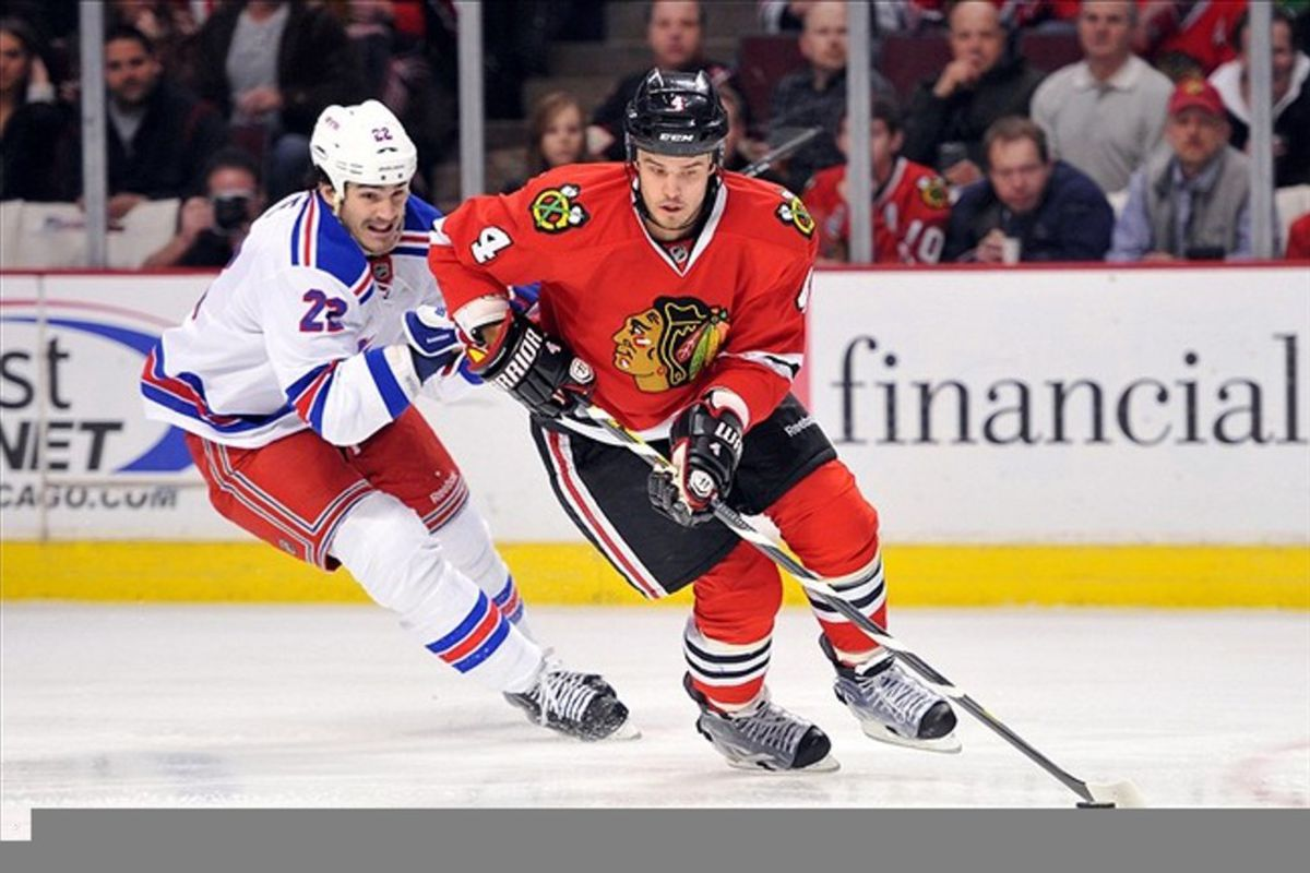 Mar 9, 2012; Chicago, IL, USA; Chicago Blackhawks defenseman Niklas Hjalmarsson (4) is defended by New York Rangers center Brian Boyle (22)  during the first period at the United Center. Mandatory Credit: Rob Grabowski-US PRESSWIRE
