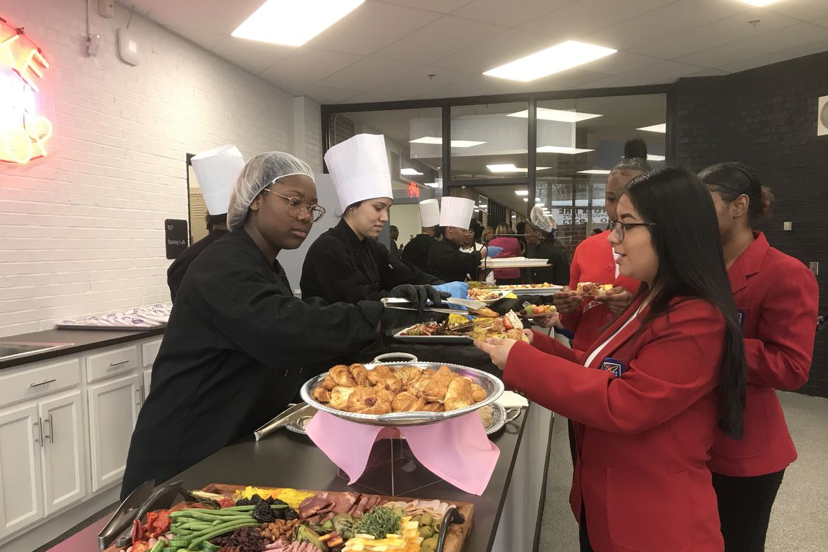 A student wearing a hair net and two wearing chefs hats serve people in line at a buffet table.