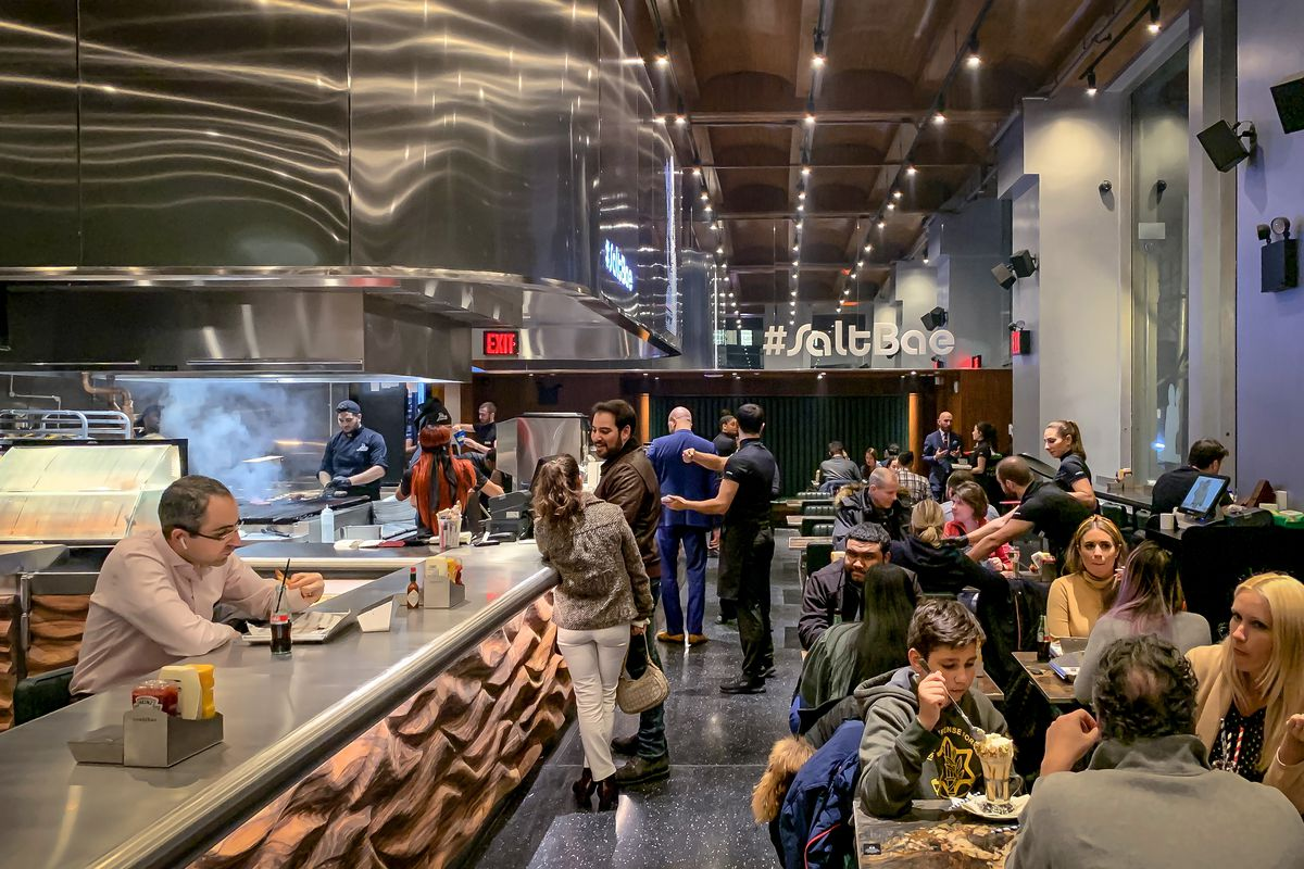 Patrons sit at tables and at a counter at the reasonably full dining room at Salt Bae, while grill workers in the open kitchen
