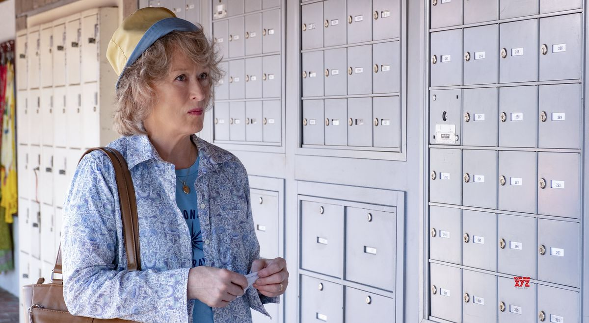 Streep stands in front of rows and rows of mailboxes.