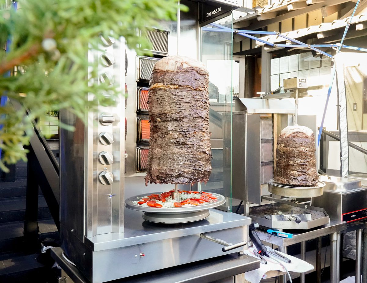 Two stands of shawarma surrounded by a leafy tree.