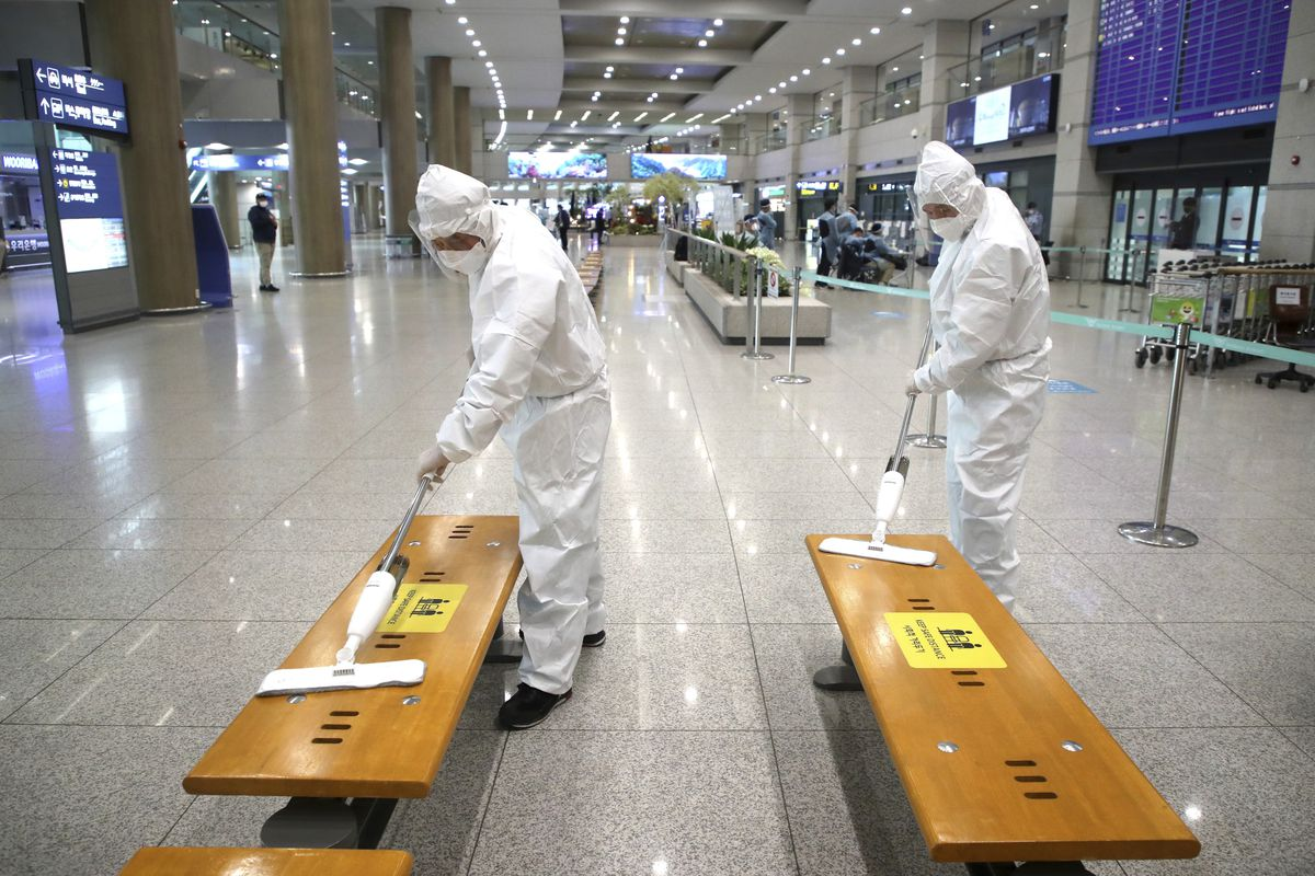 Workers wearing protective gears disinfect chairs as a precaution against the coronavirus at the arrival hall of the Incheon International Airport in Incheon, South Korea, Monday, Dec. 28, 2020.