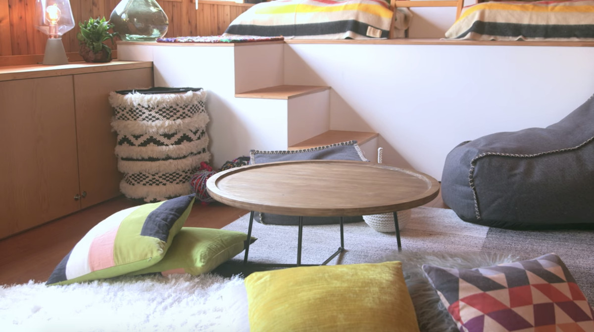 Multiple assorted pillows are on the floor of a room. There is a grey and white area rug on the floor. The pillows are arranged around a wooden table.