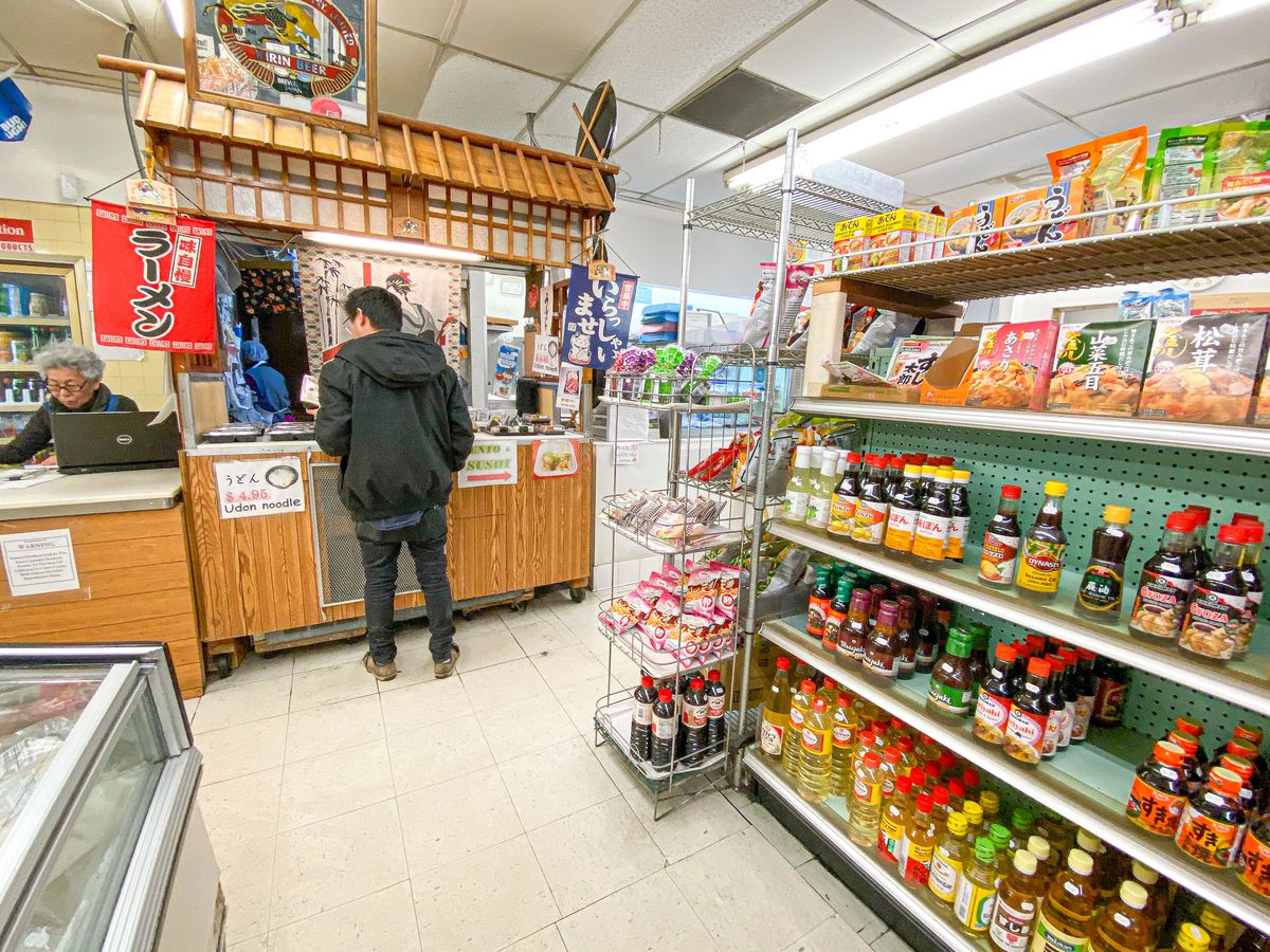 A customer waits for food inside of a small Japanese market lined with soy sauce on the shelves.