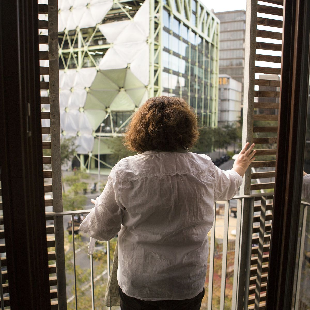 Pilar, a local resident, looks out from her apartment window onto the Poblenou superblock.