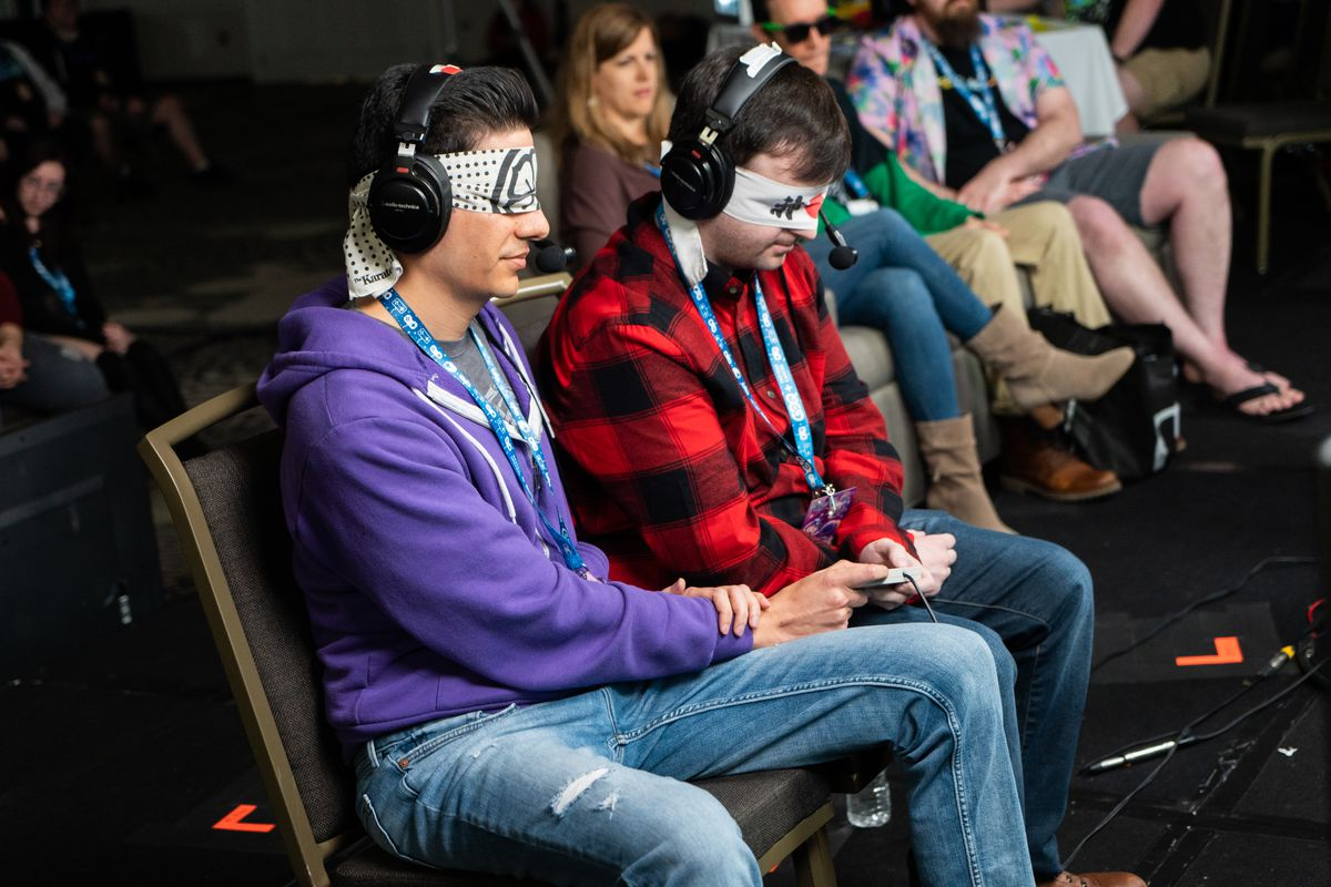 Two blindfolded gamers with headphones, one wearing a blue hoodie, the other a red plaid hunting jacket, crouch over a single controller as they try to beat a game together.