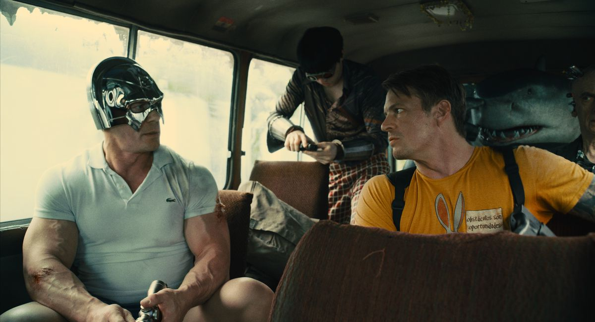 Peacemaker, in casual clothes and his helmet, and Col. Rick Flag sit in a crowded bus with King Shark in The Suicide Squad.