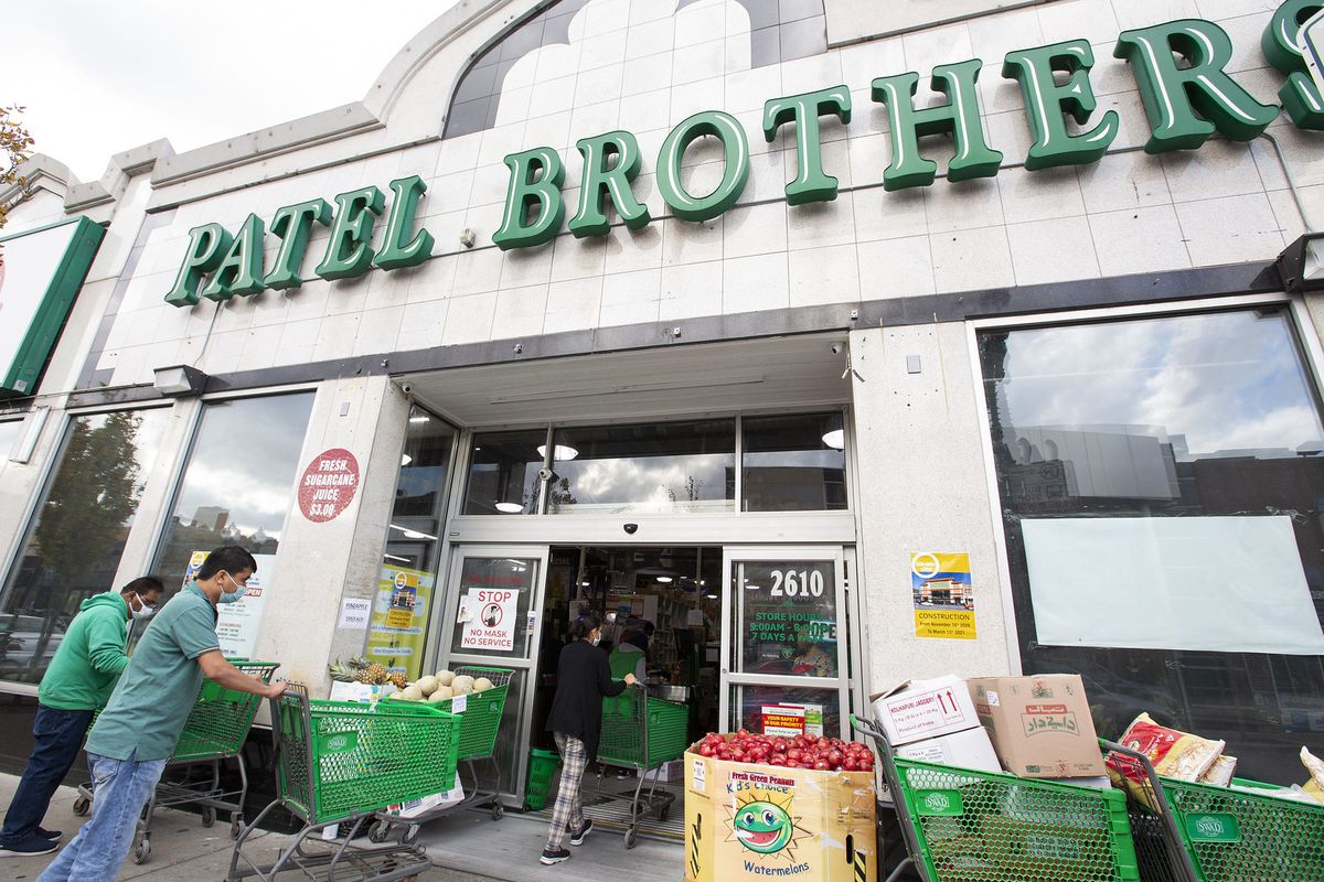 "A storefront entrance with ""Patel Brothers"" written in a green sign."