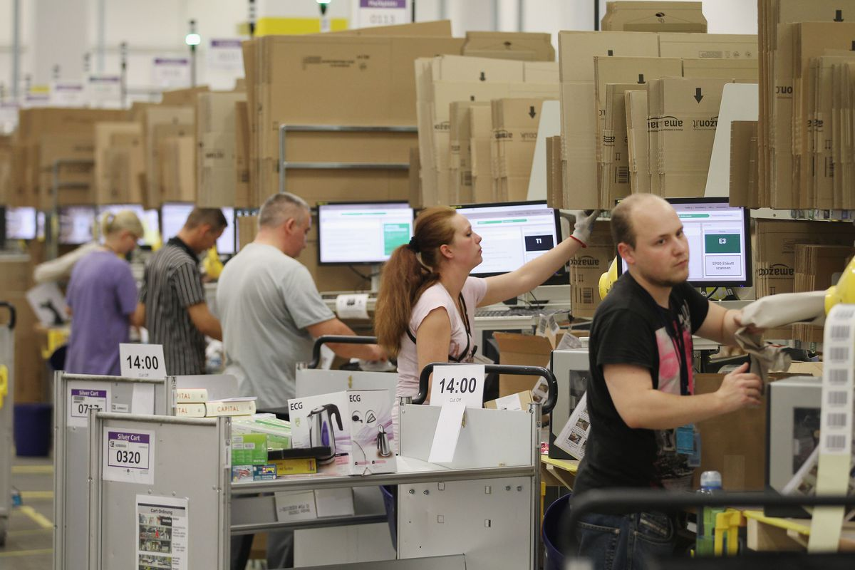 Several Amazon workers at a warehouse scan stacks of packages on the shop floor