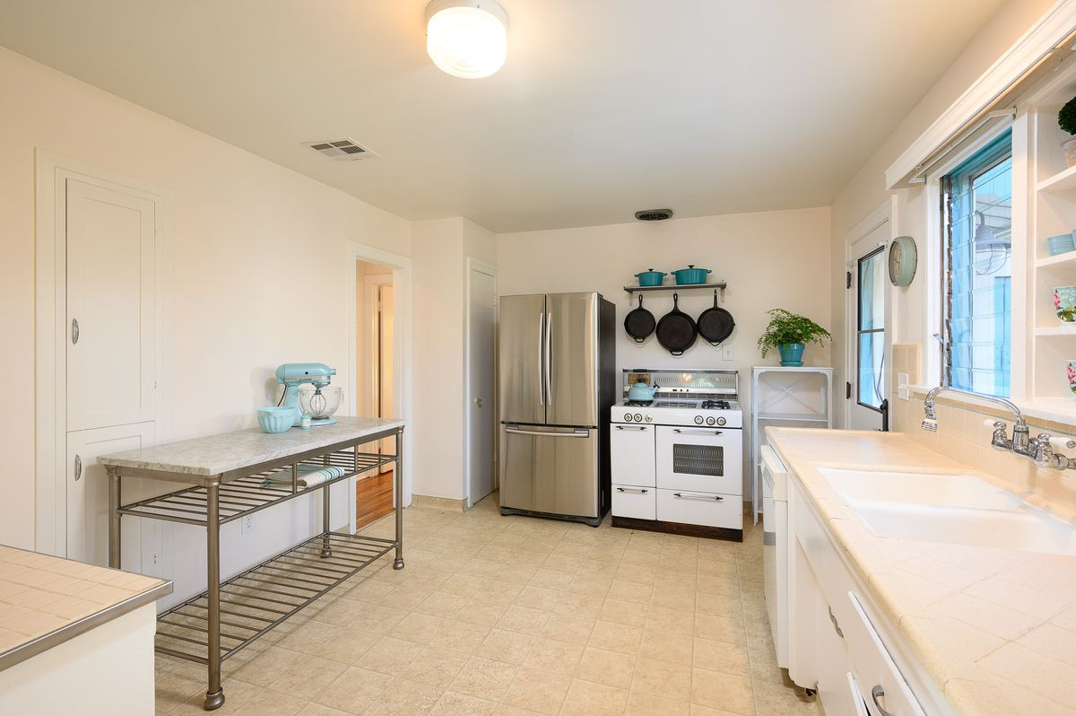 A large rectangular kitchen with white cabinets, peach tile countertops, beige tiled floors, a stainless steel oven, and a vintage stove.