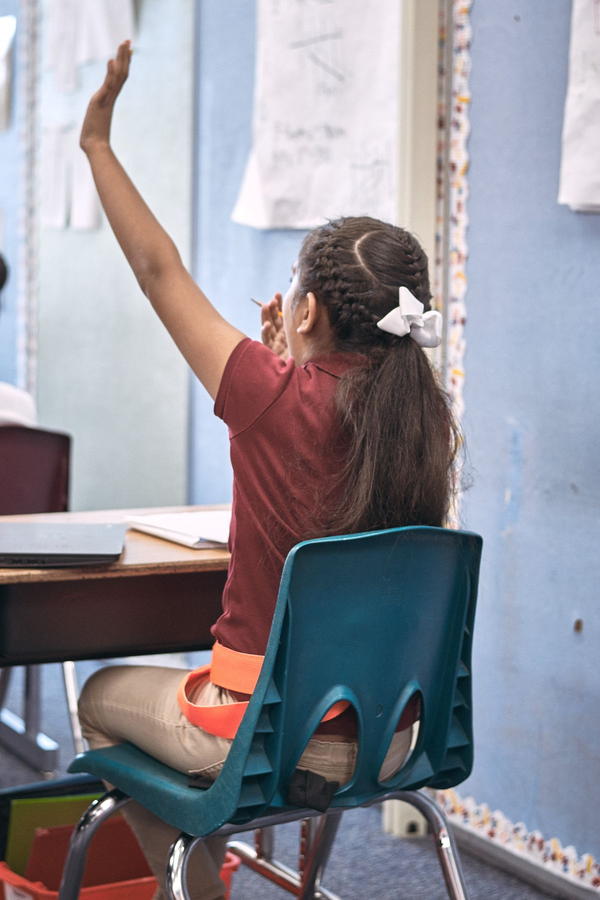 A McGlone student raises her hand in class.