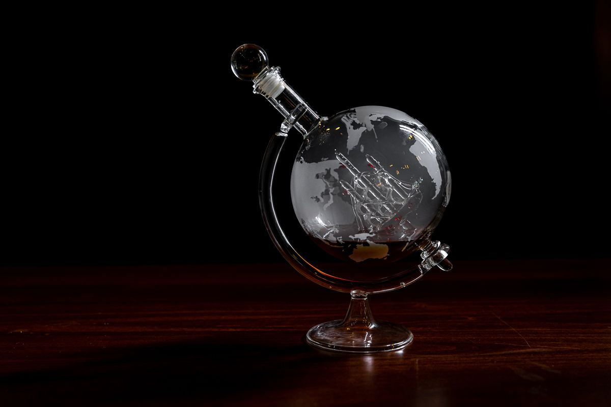 Brown liquid sits in a round glass container shaped like a globe with continents and a ship etched on it.