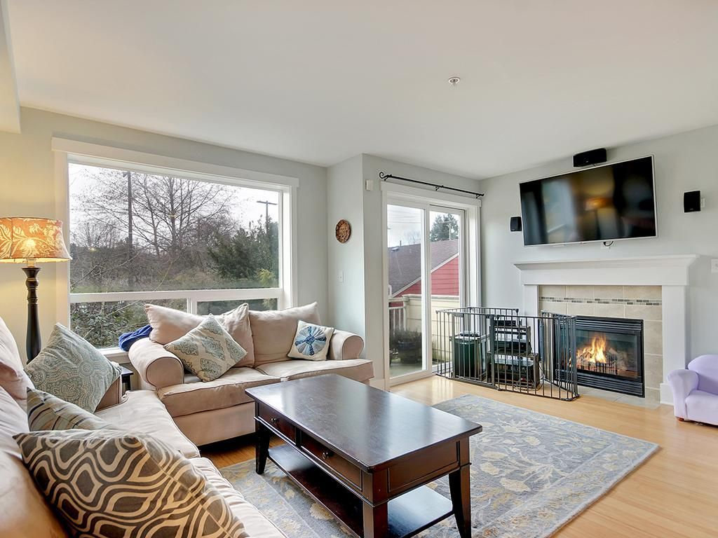 A living area with a fireplace, large windows, and a sliding glass door.