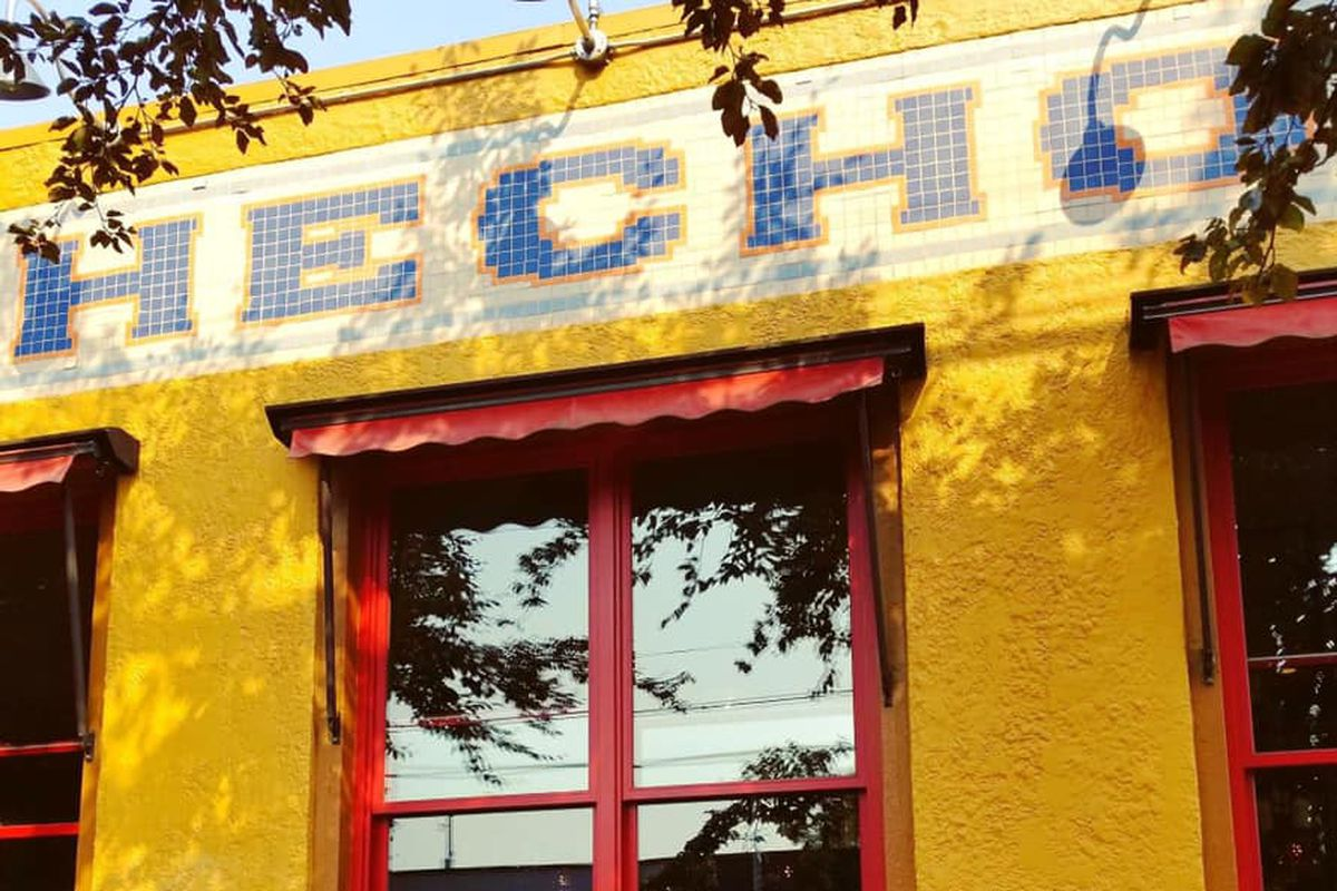 The yellow-painted exterior of Hecho restaurant in Seattle
