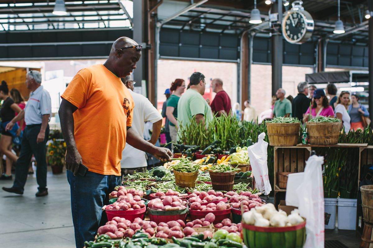 A man in an orange shirt, jeans, and sunglasses picks out produce inside of the Eastern Market sheds.