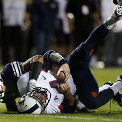 Sione Takitaki (16) of Brigham Young  sacks quarterback Bryant Shirreffs (4) of the Connecticut Huskies during NCAA football in Provo, Friday, Oct. 2, 2015.