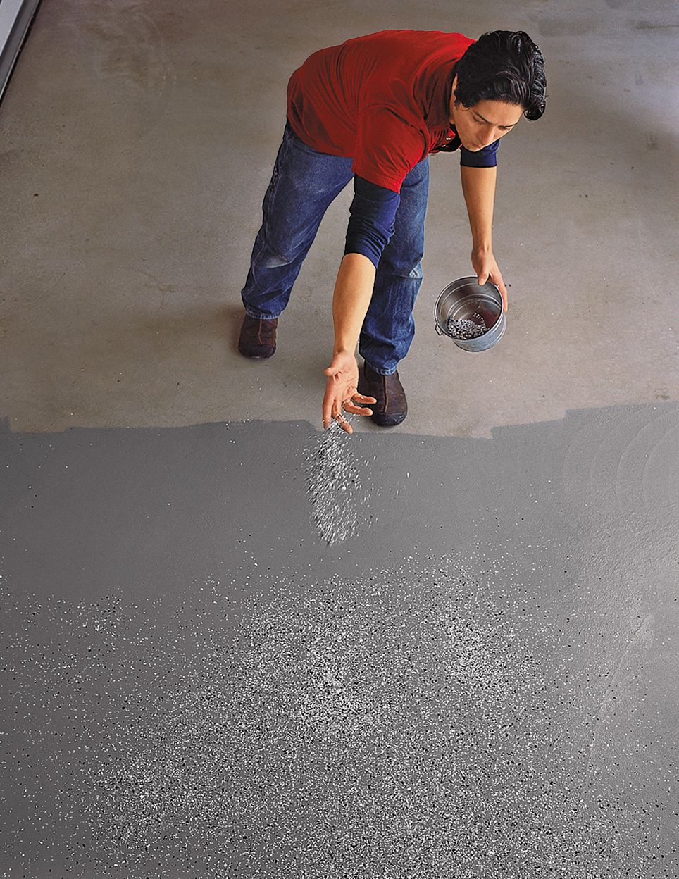 Person sprinkling color flakes onto the garage floor by hand.