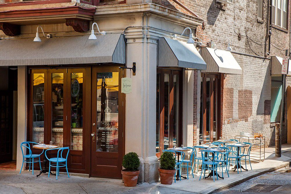 corner restaurant with awning and blue sidewalk tables