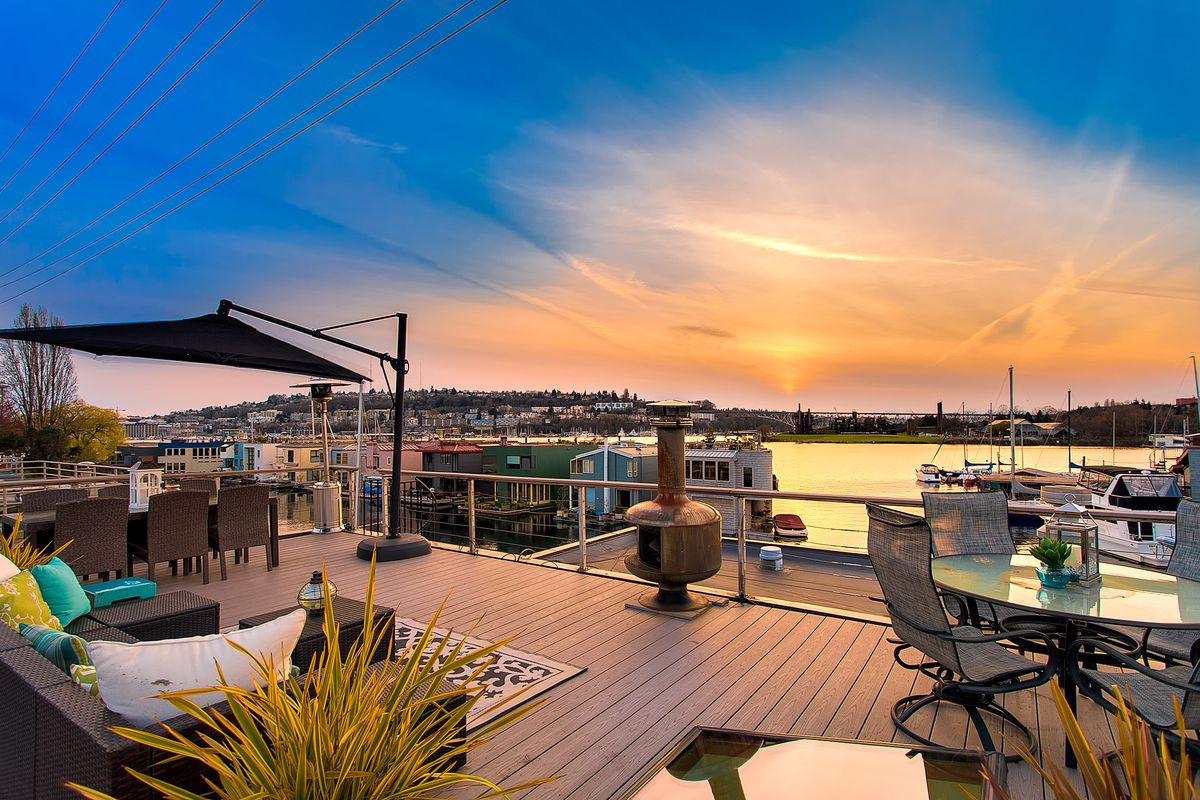 A roof deck features soft seating, two tables, and an outdoor fireplace.