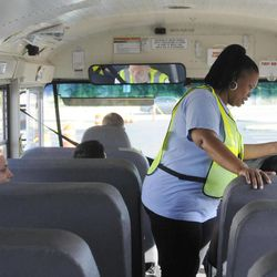 In this photo taken Aug. 18, 2012, Dorcinica Riley, center, a bus monitor in the district, participates during an open house for parents and students riding the bus for the first time this school year, at the Buffalo Academy for Visual and Performing Arts, in Buffalo, N.Y. The cell phone video of a bus monitor's cruel taunting, in June, ignited a global outpouring of support for the monitor and revulsion at her middle-school tormentors. The video raised questions about the role of bus monitors, including how much they can really do to protect against bullies while seeing riders safely on and off the bus, and how its victim, the bus monitor and supposed authority figure on the bus, could command so little respect.
