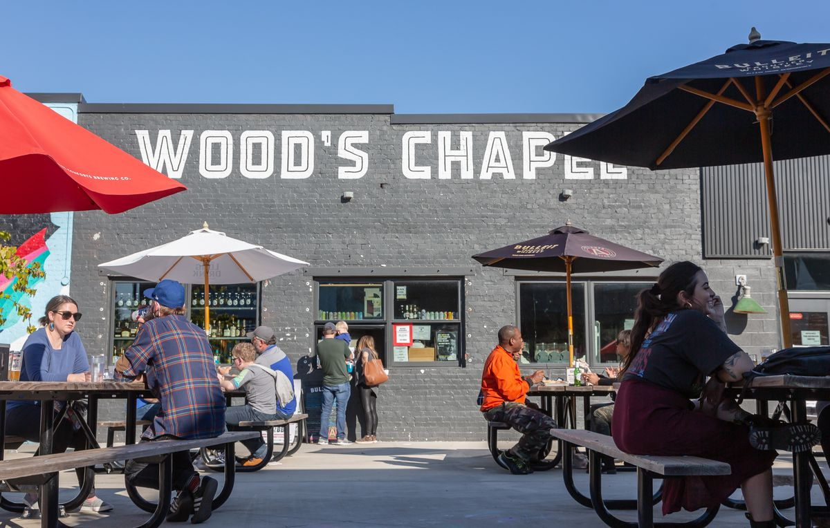 People enjoying barbecue socially distanced at picnic tables with red, black, and white umbrellas at Wood's Chapel Barbecue in Summerhill, Atlanta. The gray-black painted brick exterior of Wood's Chapel in the background with a young family standing and ordering at the to-go window