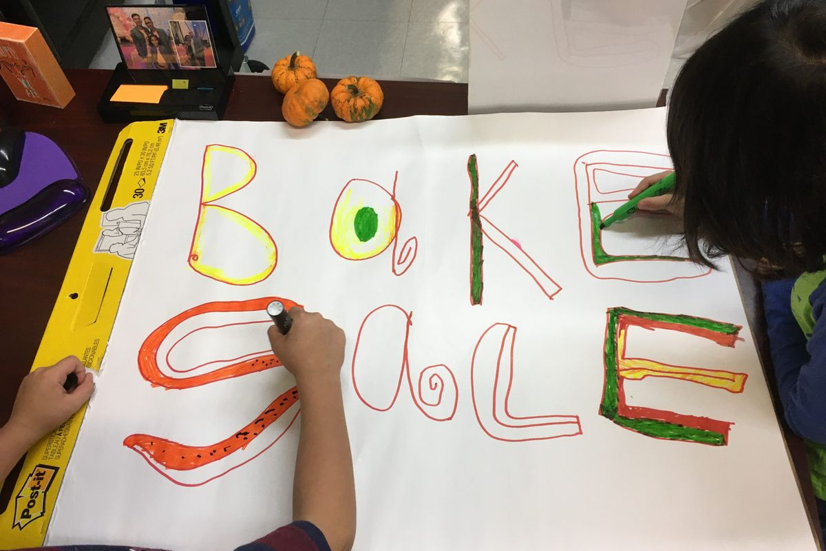 Children help color a bake sale sign for a PTA fundraiser at New York City's P.S. 165.